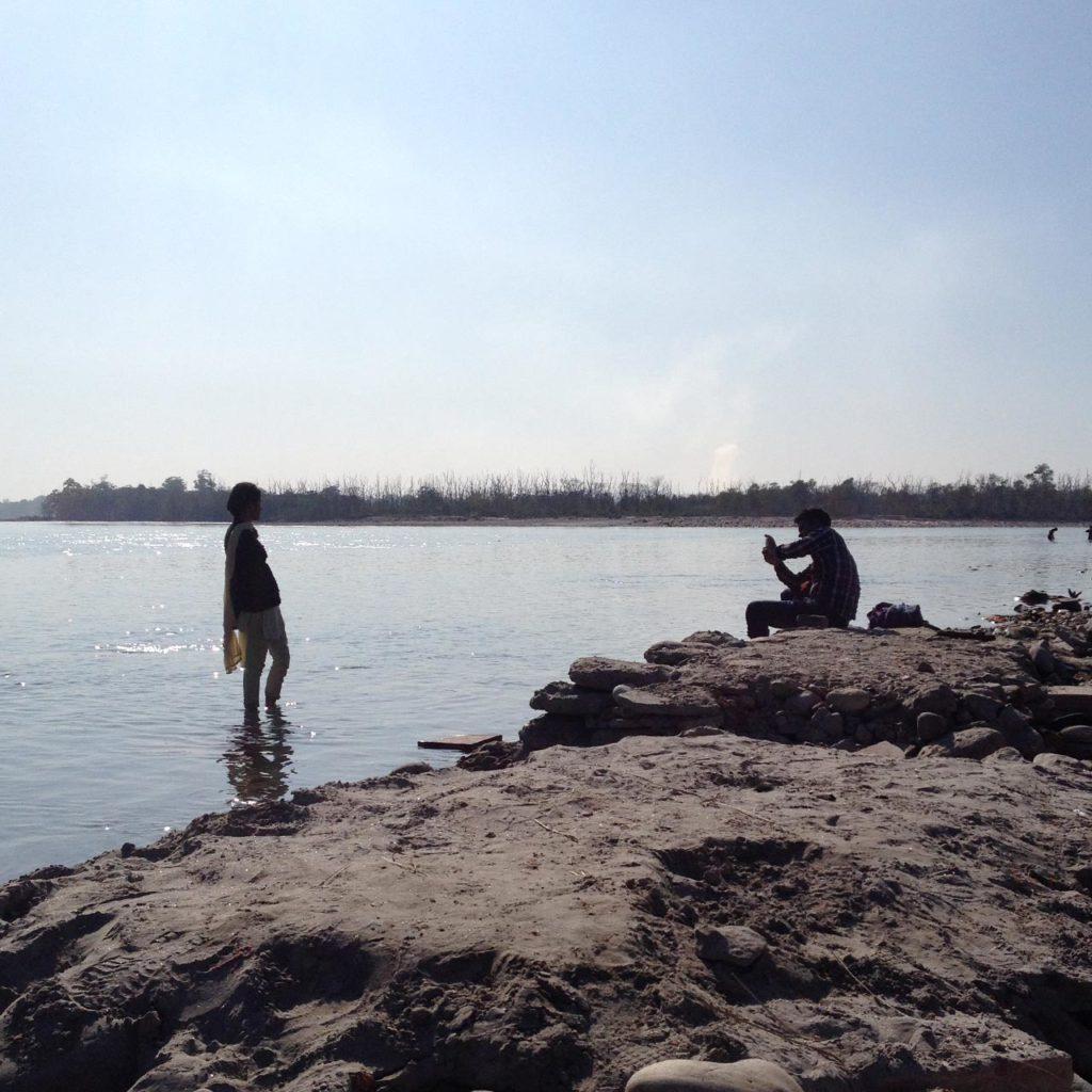 Casal tirando foto na beira do Rio em Rishikesh, Índia. Para ele, ela é quem é relevante.